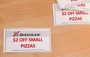 Restaurant coupons showing a $2 off deal on a small pizza, illustrating the paper coupon distribution method | SpeedLine