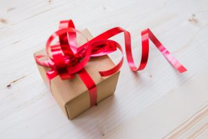 A small brown box wrapped in red ribbon, the perfect size for gift cards