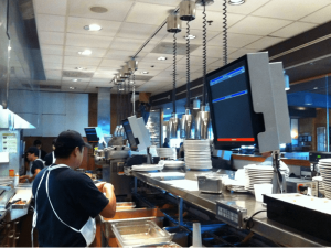 A prep station at a restaurant with a kitchen display system
