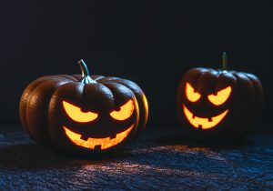 Two carved pumpkins lit up in the dark.